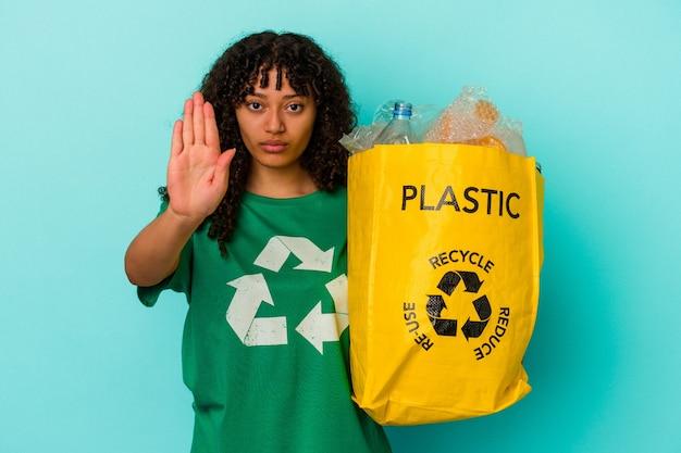 Młoda kobieta rasy mieszanej trzyma plastikową torbę z recyklingu na białym tle na niebieskim tle, stojąc z wyciągniętą ręką pokazując znak stopu, uniemożliwiając tobie.