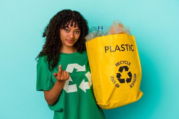 Młoda kobieta rasy mieszanej trzyma plastikową torbę z recyklingu na białym tle na niebieskim tle, wskazując palcem na ciebie, jakby zapraszając się bliżej.