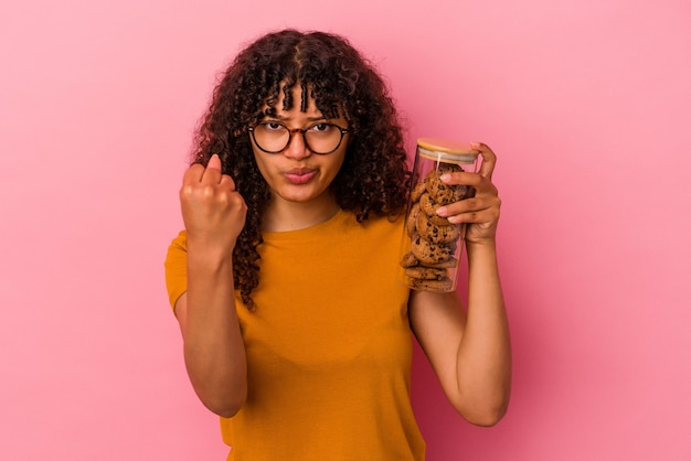 Młoda kobieta rasy mieszanej trzyma słoik ciasteczek na białym tle na różowym tle pokazując pięść do aparatu, agresywny wyraz twarzy.