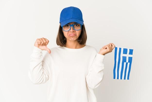 Młoda kobieta rasy mieszanej trzymając flagę grecji