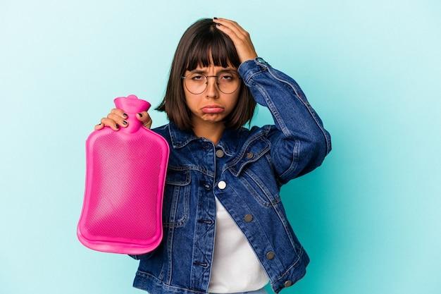Młoda kobieta rasy mieszanej trzymając gorącą wodę w butelce na białym tle na niebieskim tle będąc w szoku, przypomniała sobie ważne spotkanie.
