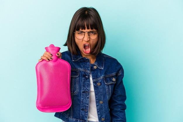 Młoda kobieta rasy mieszanej trzymając gorącą wodę w butelce na białym tle na niebieskim tle krzycząc bardzo zły i agresywny.