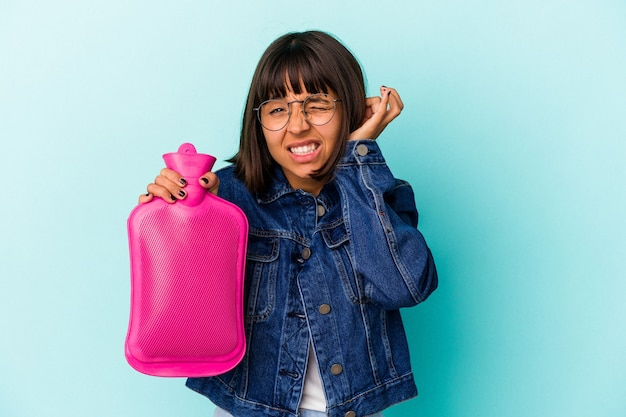 Młoda kobieta rasy mieszanej trzymając gorącą wodę w butelce na białym tle na niebieskim tle obejmujące uszy rękami.