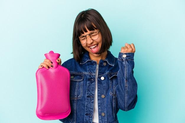 Młoda kobieta rasy mieszanej trzymając gorącą wodę w butelce na białym tle na niebieskim tle podnosząc pięść po zwycięstwie, koncepcja zwycięzca.