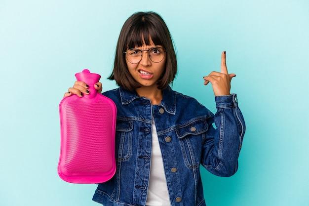 Młoda kobieta rasy mieszanej trzymając gorącą wodę w butelce na białym tle na niebieskim tle pokazując gest rozczarowania palcem wskazującym.