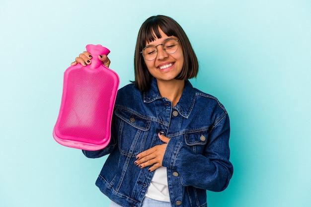 Młoda kobieta rasy mieszanej trzymając gorącą wodę w butelce na białym tle na niebieskim tle śmiechu i zabawy.