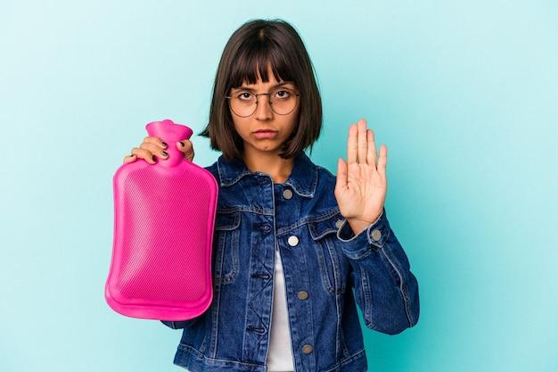 Młoda kobieta rasy mieszanej trzymając gorącą wodę w butelce na białym tle na niebieskim tle stojąc z wyciągniętą ręką pokazując znak stop, uniemożliwiając.