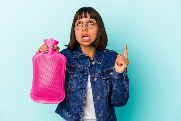 Młoda kobieta rasy mieszanej trzymając gorącą wodę w butelce na białym tle na niebieskim tle, wskazując do góry z otwartymi ustami.
