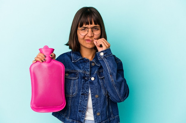 Młoda kobieta rasy mieszanej trzymając gorącą wodę w butelce na białym tle na niebieskim tle z palcami na ustach zachowując tajemnicę.