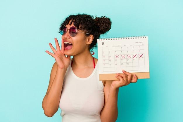 Młoda kobieta rasy mieszanej trzymając kalendarz na białym tle na niebieskim tle krzycząc i trzymając dłoń w pobliżu otwartych ust.