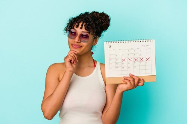 Młoda kobieta rasy mieszanej trzymając kalendarz na białym tle na niebieskim tle patrząc w bok z wyrazem wątpliwości i sceptyczny.