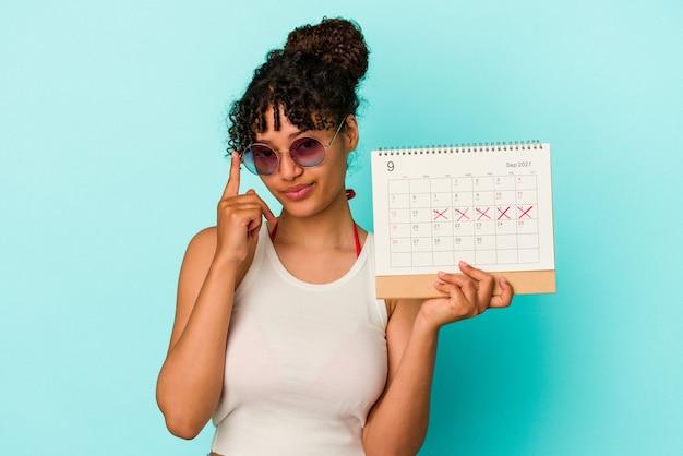 Młoda kobieta rasy mieszanej trzymając kalendarz na białym tle na niebieskim tle wskazując świątynię palcem, myśląc, koncentruje się na zadaniu.