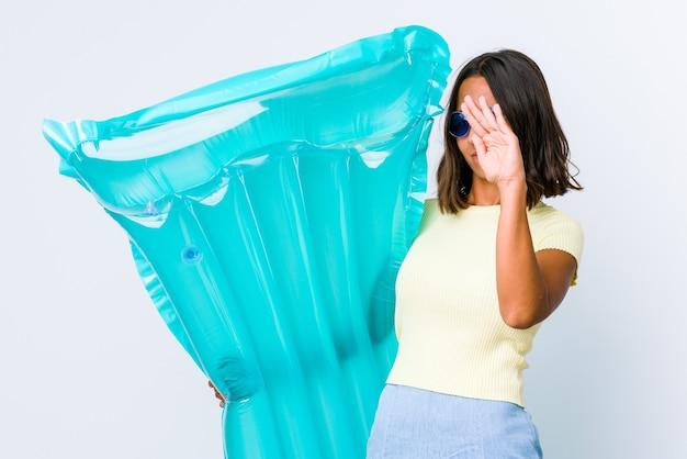 Młoda kobieta rasy mieszanej trzymając materac powietrza, trzymając dwie skrzyżowane ręce, koncepcja odmowy.