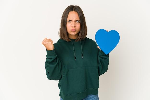 Młoda kobieta rasy mieszanej trzymając niebieskie serce na białym tle