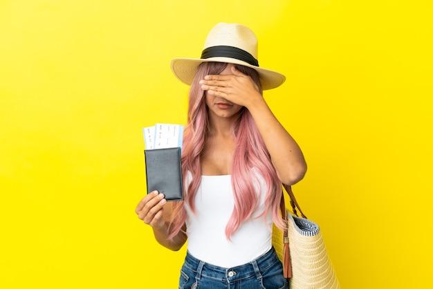 Młoda kobieta rasy mieszanej trzymając paszport i torbę plażową na białym tle na żółtym tle zasłaniając oczy rękami. nie chcę czegoś widzieć