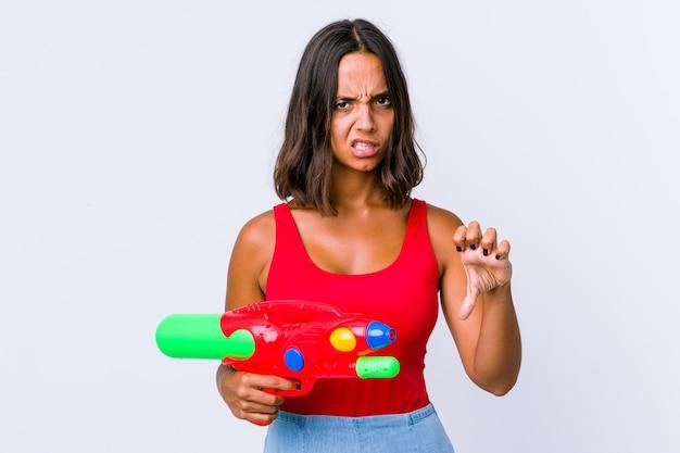 Młoda kobieta rasy mieszanej trzymając pistolet na wodę na białym tle pokazując kciuk w dół i wyrażając niechęć.
