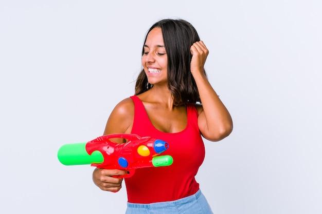 Młoda kobieta rasy mieszanej trzymając pistolet na wodę na białym tle świętuje zwycięstwo, pasję i entuzjazm, szczęśliwy wyraz.