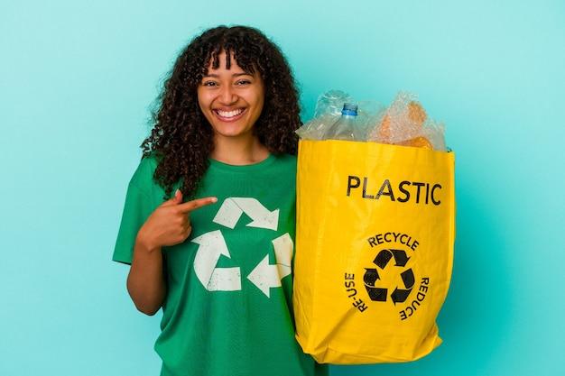 Młoda kobieta rasy mieszanej, trzymając plastikową torbę z recyklingu odizolowaną na niebieskiej ścianie, uśmiechając się i wskazując na bok, pokazując coś w pustym miejscu.