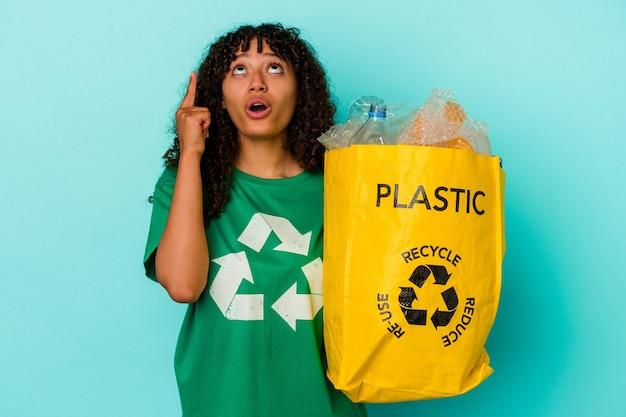 Młoda kobieta rasy mieszanej, trzymając plastikową torbę z recyklingu samodzielnie na niebieskiej ścianie, skierowaną do góry z otwartymi ustami.