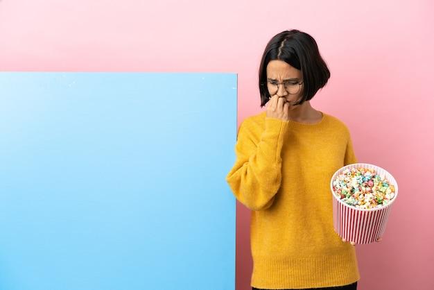 Młoda kobieta rasy mieszanej trzymając popcorns z dużym sztandarem na białym tle, mając wątpliwości
