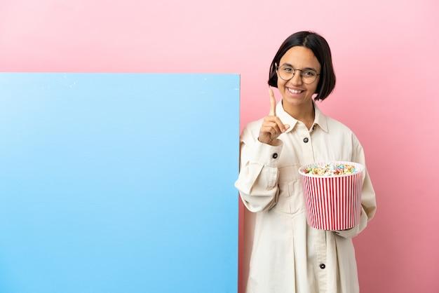 Młoda kobieta rasy mieszanej trzymając popcorns z dużym sztandarem na białym tle pokazując i podnosząc palec