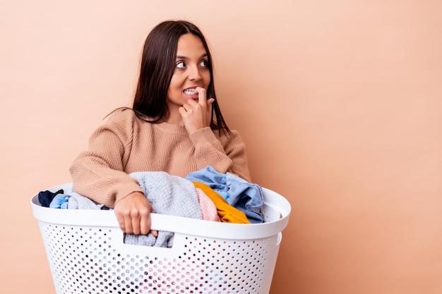 Młoda kobieta rasy mieszanej trzymając pranie na białym tle zrelaksowany myślenie o czymś patrząc na przestrzeń kopii.