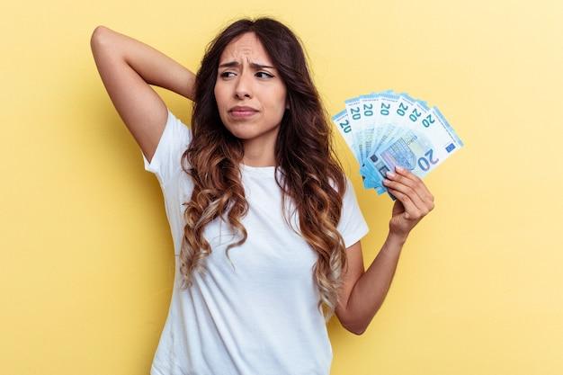 Młoda kobieta rasy mieszanej trzymając rachunki na białym tle na żółtym tle dotykając tyłu głowy, myśląc i dokonując wyboru.