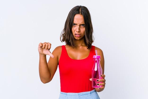 Młoda kobieta rasy mieszanej trzymając shake mleka na białym tle pokazując kciuk w dół i wyrażając niechęć.
