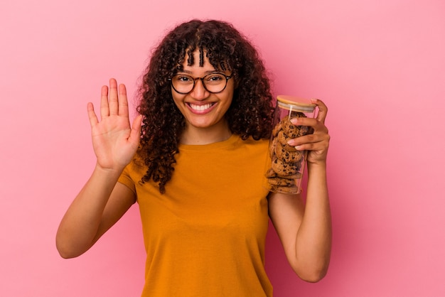 Młoda kobieta rasy mieszanej trzymając słoik ciasteczka na białym tle na różowym tle uśmiechnięty wesoły pokazując numer pięć palcami.