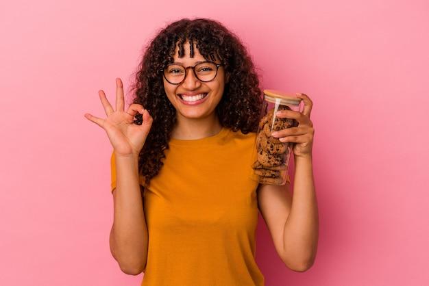 Młoda kobieta rasy mieszanej trzymając słoik ciasteczka na białym tle na różowym tle wesoły i pewny siebie pokazując ok gest.