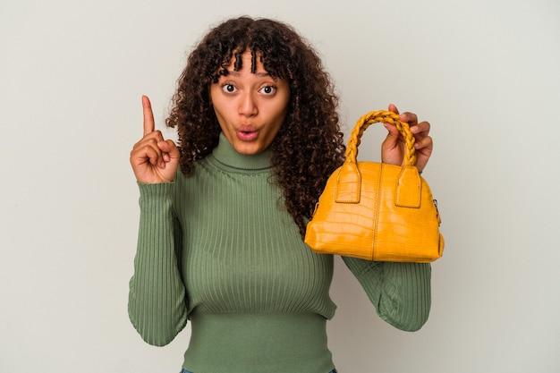 Młoda kobieta rasy mieszanej trzymając torebkę na białym tle na białej ścianie, mając jakiś świetny pomysł, pojęcie kreatywności.