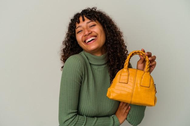 Młoda kobieta rasy mieszanej trzymając torebkę na białym tle na białej ścianie śmiejąc się i zabawy.