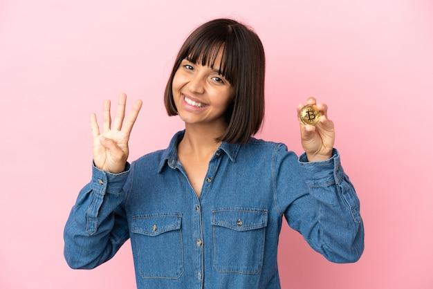 Młoda kobieta rasy mieszanej trzymająca bitcoin na białym tle szczęśliwa i licząca cztery palcami