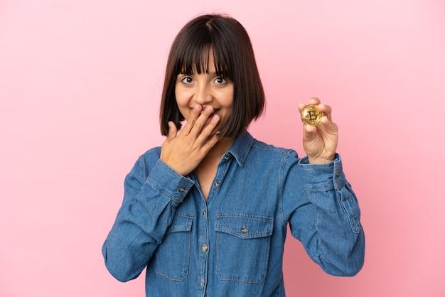 Młoda kobieta rasy mieszanej trzymająca na białym tle bitcoin szczęśliwa i uśmiechnięta zakrywająca usta dłonią