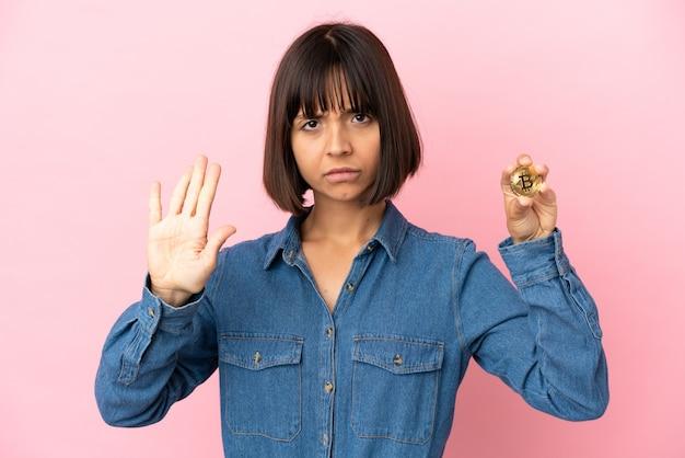 Młoda kobieta rasy mieszanej, trzymająca na białym tle bitcoin, wykonująca gest zatrzymania