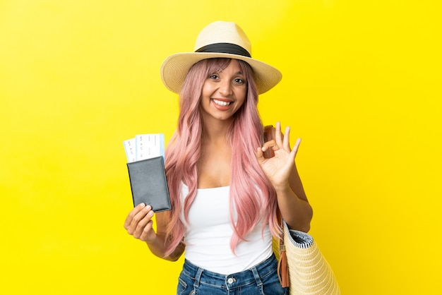 Młoda kobieta rasy mieszanej trzymająca paszport i torbę plażową na białym tle na żółtym tle pokazując znak ok palcami