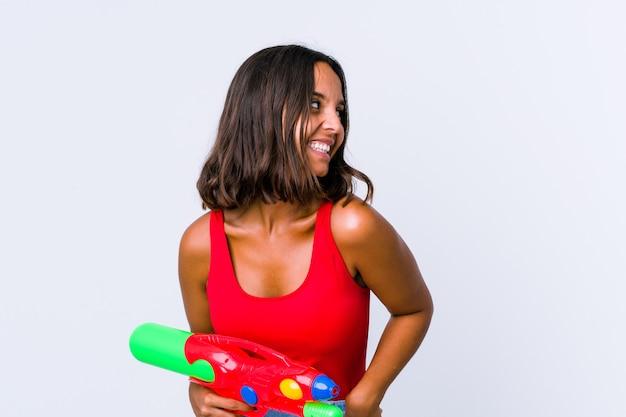 Młoda kobieta rasy mieszanej trzymająca pistolet na wodę na białym tle śmieje się i zamyka oczy, czuje się zrelaksowana i szczęśliwa.