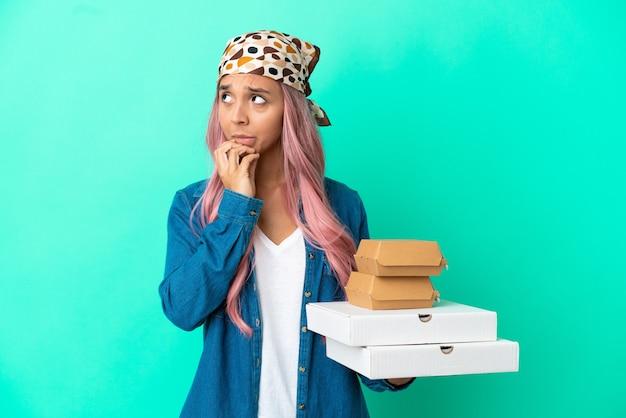Młoda kobieta rasy mieszanej trzymająca pizze i hamburgery na zielonym tle, mająca wątpliwości i myśląca
