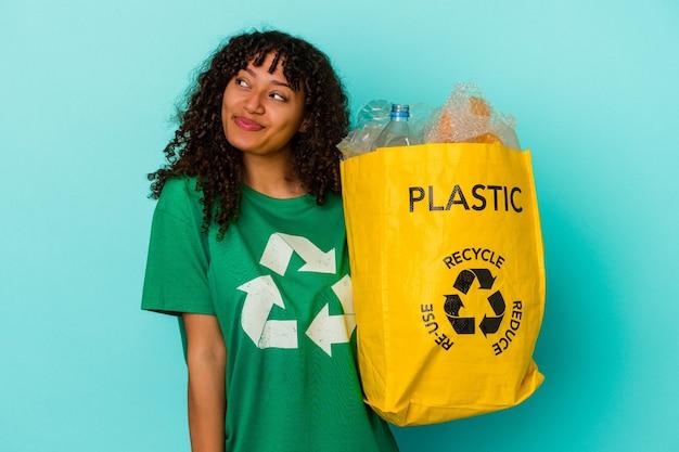 Młoda kobieta rasy mieszanej trzymająca plastikową torbę z recyklingu na białym tle na niebieskim tle, marzącą o osiągnięciu celów i celów