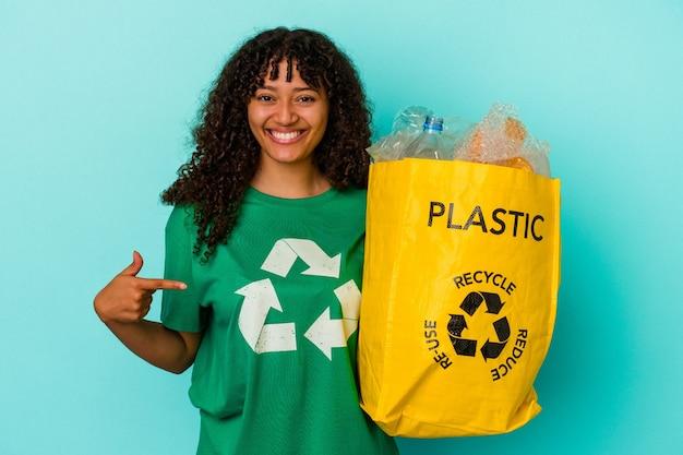 Młoda kobieta rasy mieszanej trzymająca plastikową torbę z recyklingu na białym tle na niebieskim tle osoba wskazująca ręcznie na miejsce na koszulkę, dumna i pewna siebie