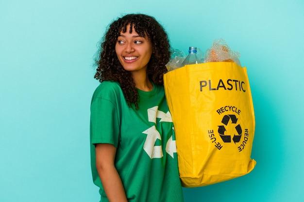 Młoda kobieta rasy mieszanej trzymająca plastikową torbę z recyklingu na białym tle na niebieskim tle wygląda na uśmiechniętą, wesołą i przyjemną.