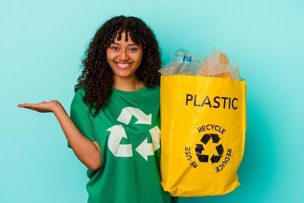 Młoda kobieta rasy mieszanej trzymająca plastikową torbę z recyklingu na białym tle na niebieskim tle z miejscem na kopię na dłoni i trzymająca drugą rękę w talii.