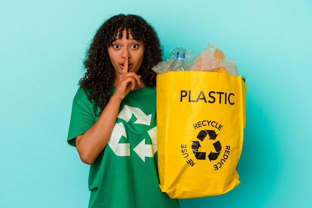 Młoda kobieta rasy mieszanej trzymająca plastikową torbę z recyklingu na białym tle na niebieskim tle, zachowując tajemnicę lub prosząc o ciszę.