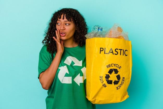 Młoda kobieta rasy mieszanej trzymająca plastikową torbę z recyklingu odizolowaną na niebieskim tle mówi tajne gorące wiadomości o hamowaniu i patrzy na bok