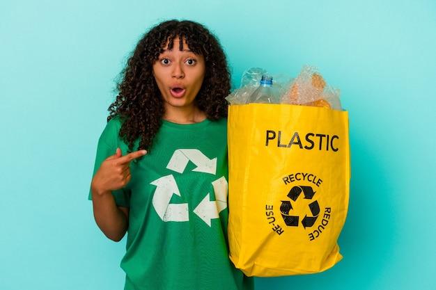Młoda kobieta rasy mieszanej trzymająca plastikową torbę z recyklingu odizolowaną na niebieskim tle skierowaną w bok