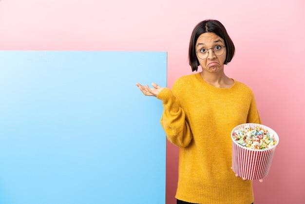 Młoda kobieta rasy mieszanej trzymająca popcorny z dużym banerem na białym tle, mająca wątpliwości podczas podnoszenia rąk
