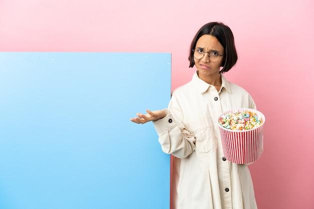 Młoda kobieta rasy mieszanej trzymająca popcorny z dużym banerem na białym tle, mająca wątpliwości
