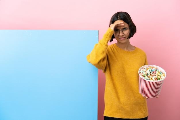 Młoda kobieta rasy mieszanej trzymająca popcorny z dużym banerem na białym tle, patrząca daleko ręką, aby coś wyglądać