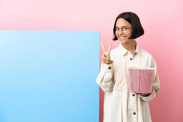 Młoda kobieta rasy mieszanej trzymająca popcorny z dużym banerem na białym tle, uśmiechnięta i pokazująca znak zwycięstwa
