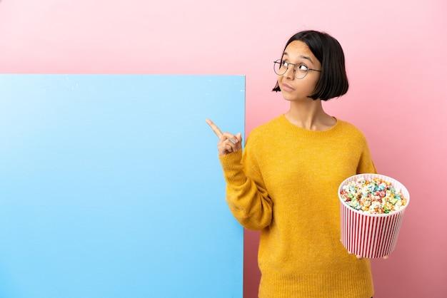 Młoda kobieta rasy mieszanej trzymająca popcorny z dużym banerem na białym tle wskazującym świetny pomysł